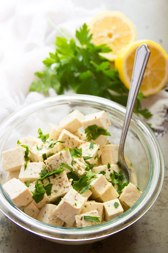 Tofu Feta Cheese in a Bowl with Spoon and Fresh Herbs and Lemon in the Background