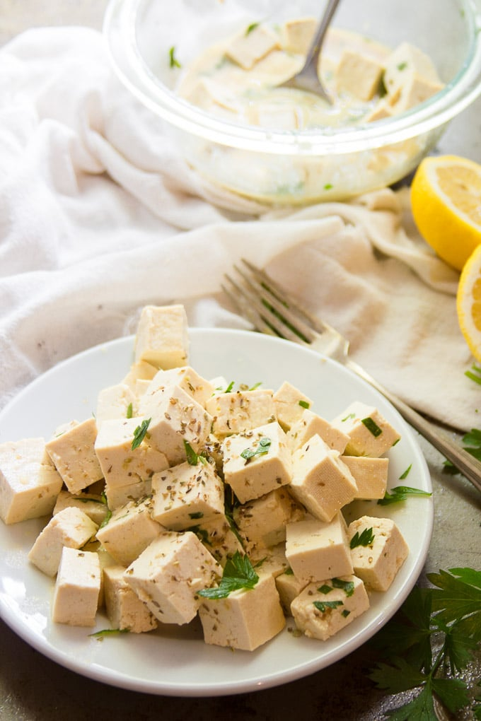 Tofu Feta on a Plate with Fork and Lemon Slices in the Background