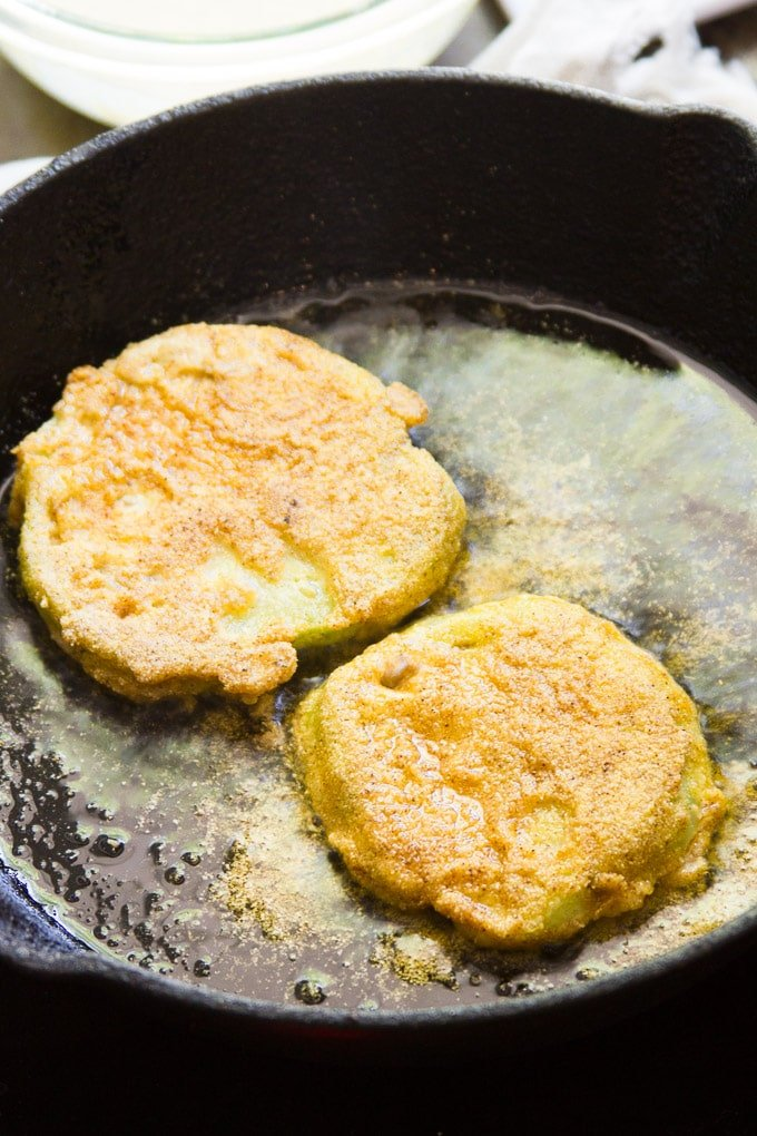 Vegan Fried Green Tomatoes Sizzling in a Skillet to Make Fried Green Tomato Sandwiches with Pimento Cashew Cheese