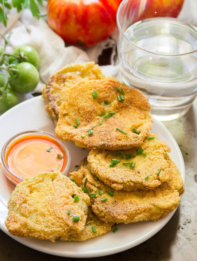 Vegan Fried Green Tomatoes on a Plate with Fresh Tomatoes and Water Glass in the Background