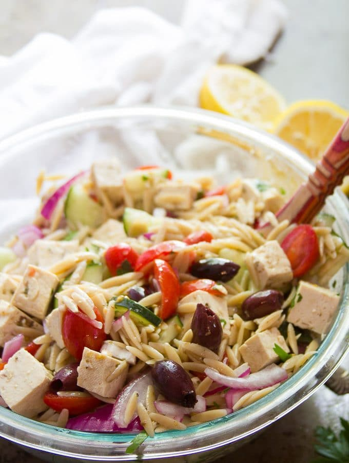 Serving Bowl Filled with Vegan Greek Orzo Salad With Spoon