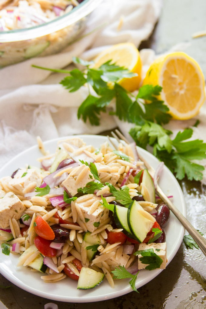 Vegan Greek Orzo Salad on a Plate with Lemon Halves and Parsley in the Background
