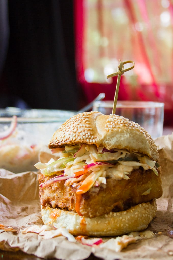 """""""Chicken"""" Fried Tofu Sandwich with Spicy Buffalo Slaw with Drinking Glass and Mixing Bowl in the Background"""