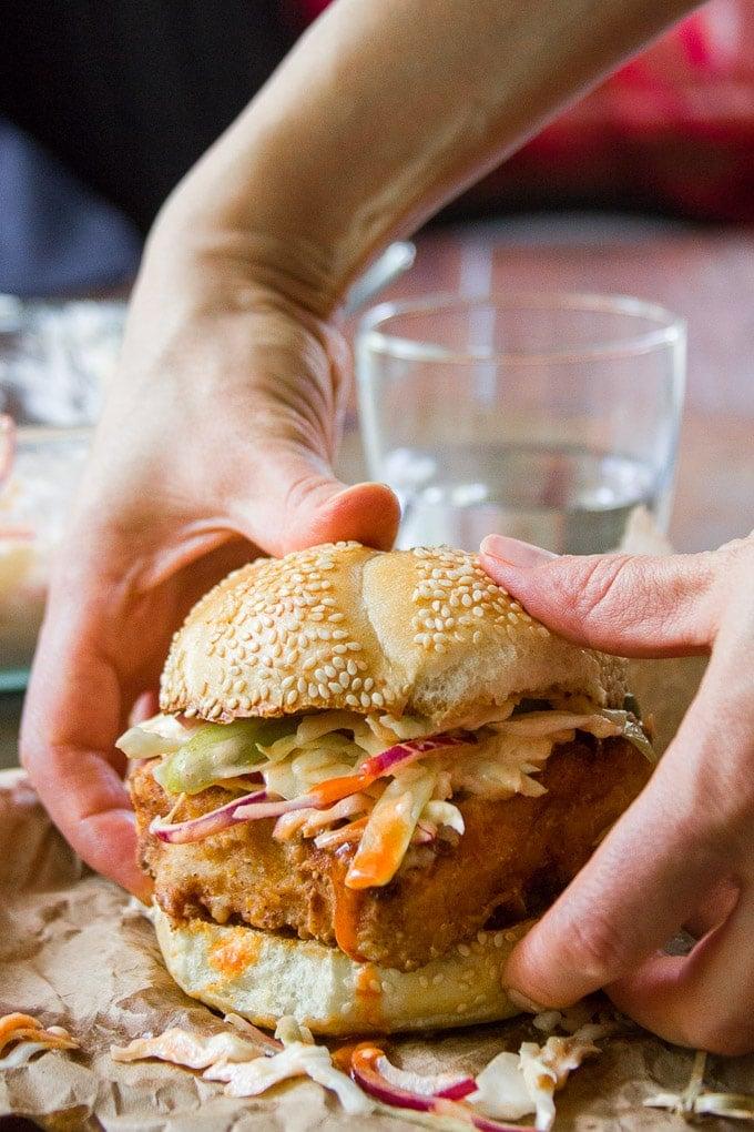 "Hands Grabbing a ""Chicken"" Fried Tofu Sandwich with Spicy Buffalo Slaw"