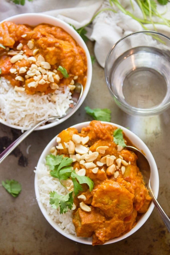 Overhead Shot of Two Bowls of Smoky Tofu, Peanut Butter & Plantain Curry with Drinking Glass and Spoons