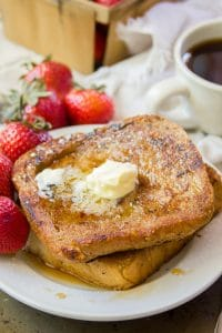 Classic Vegan French Toast on a Plate with Strawberries and Coffee Cup in the Background