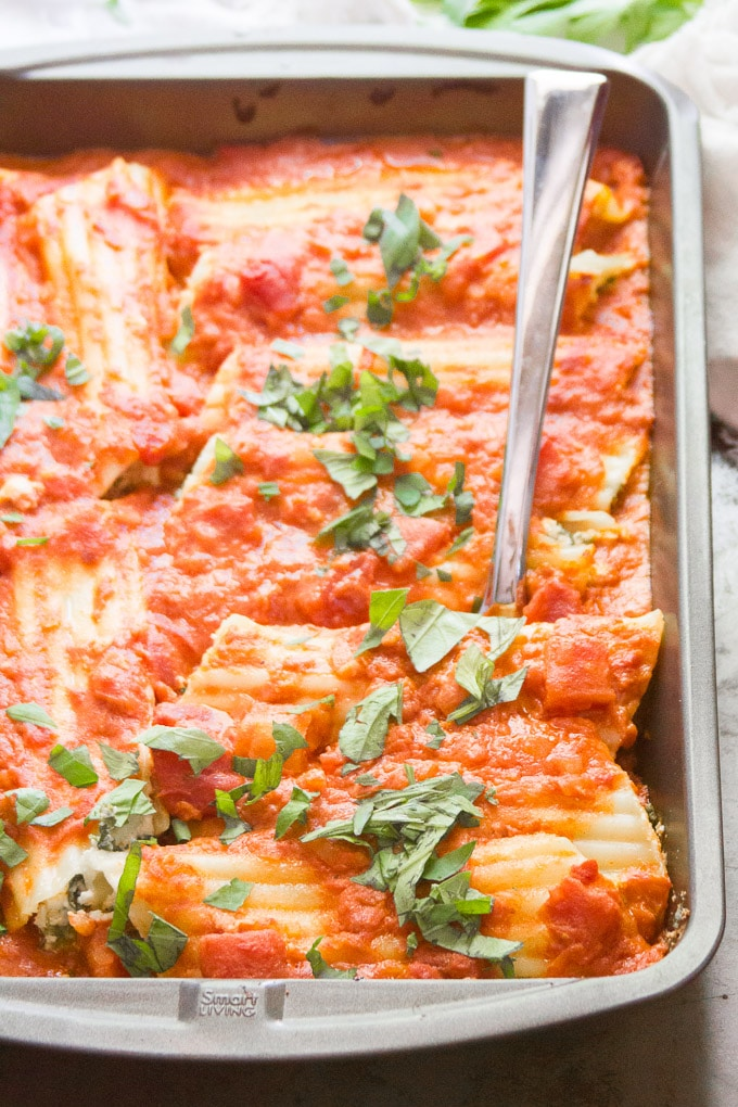 Vegan Manicotti with Blush Sauce and Kale in a Pan with Serving Spoon