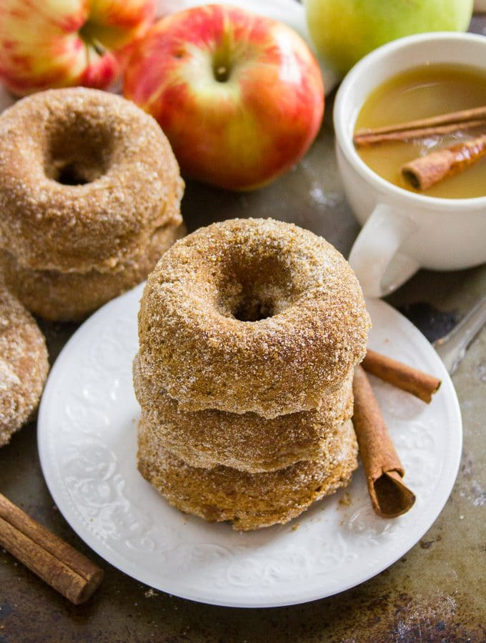 Stack of Vegan Apple Cider Doughnuts on a Plate with Cinnamon Sticks