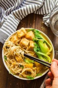 Hand with Chopsticks Grabbing a Bunch of Noodles from a Bowl of Warming Pumpkin Ramen