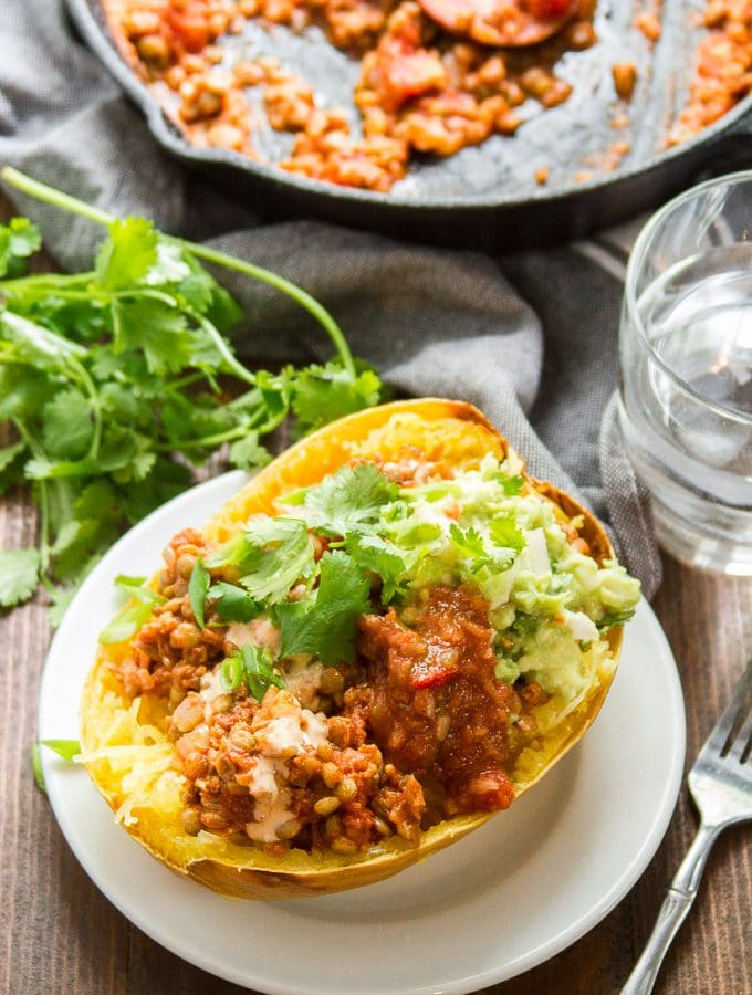 Taco Stuffed Spaghetti Squash on a Plate with Drinking Glass and Skillet in the Background