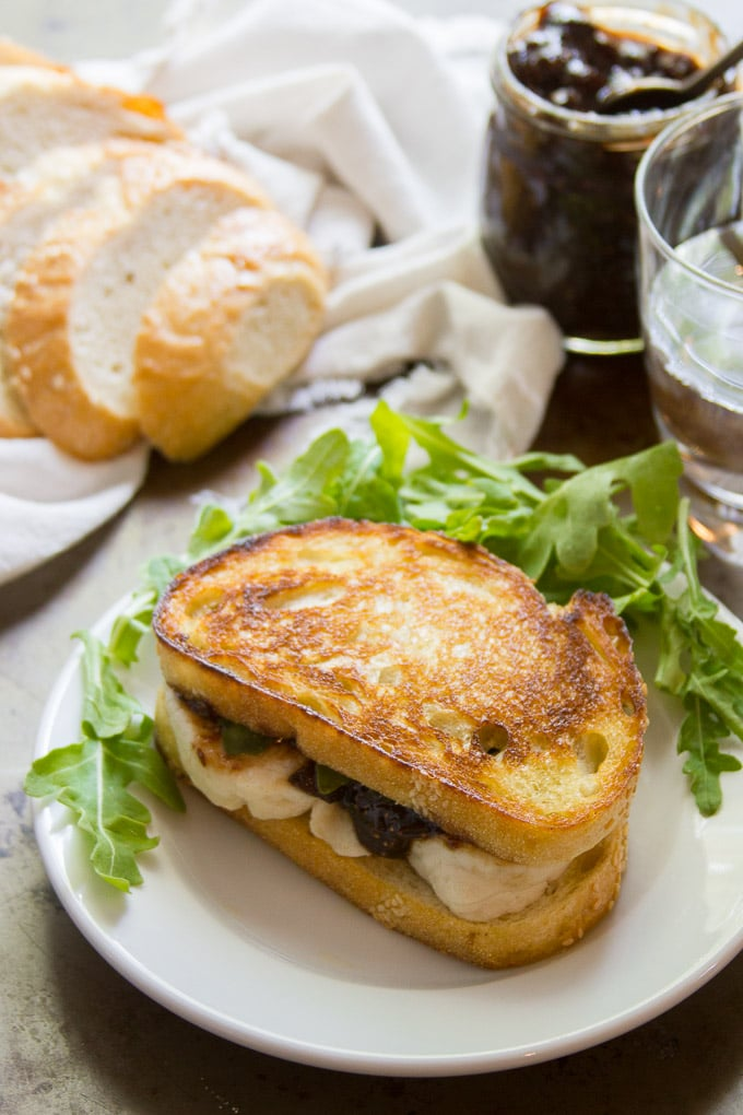 Vegan Mozzarella & Fig Jam Grilled Cheese on a Plate with Arugula and a Loaf of Bread in the Background