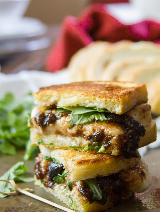 Two Halves of A Vegan Mozzarella & Fig Jam Grilled Cheese Sandwich Stacked on a Plate