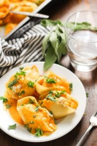 Vegan Butternut Squash Stuffed Shells on a Plate with Fork, Napkin and Drinking Glass