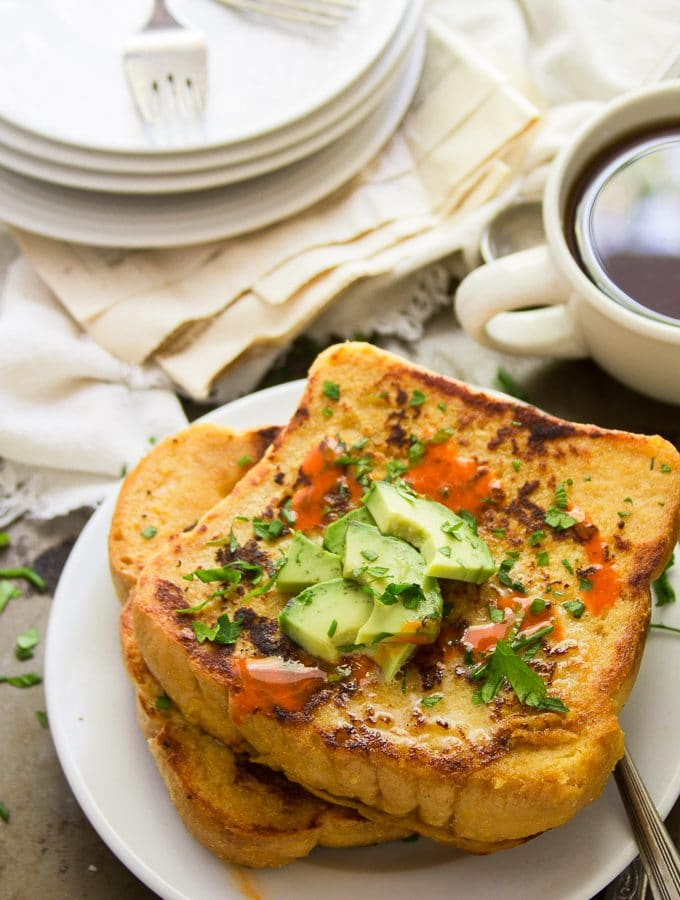 Savory Vegan French Toast on a Plate with a Stack of Dishes and Coffee Cup in the Background