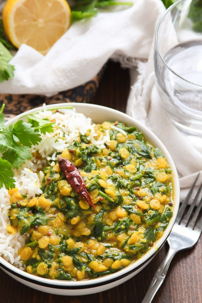 Close Up of a Bowl of Spinach Dal Topped with Cilantro and a Dried Chile Pepper