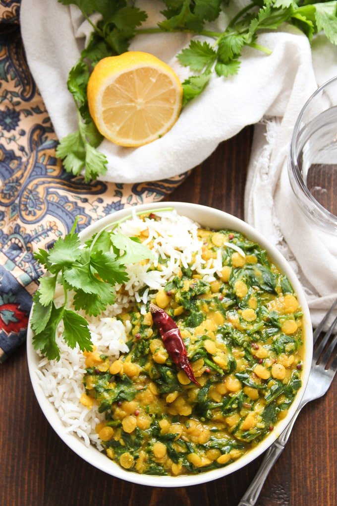 Bowl of Spinach Dal on a Table with Water Glass, Cilantro, and Lemon Half