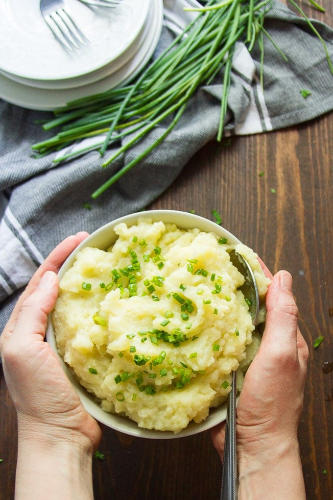 Hands Holding a Bowl of Truffled Mashed Potatoes Over a Dinner Table