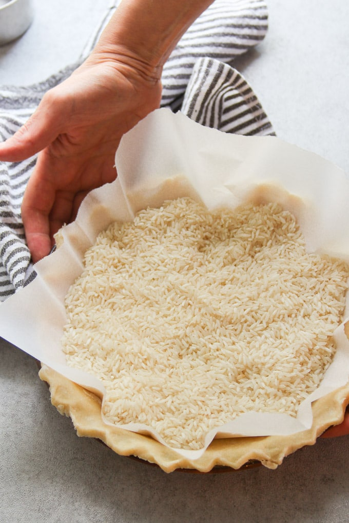 Hands Holding a Pie Crust Filled with Rice for Pre-Baking