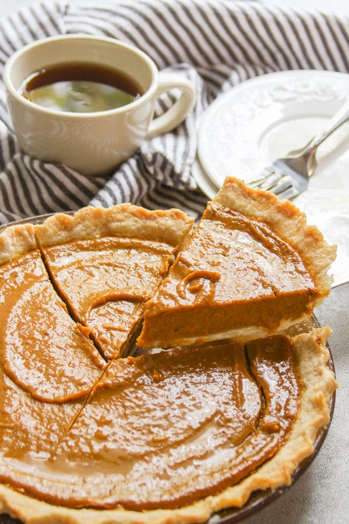A Slice of Vegan Pumpkin Pie Being Lifted from a Pie Plate with a Pie Server