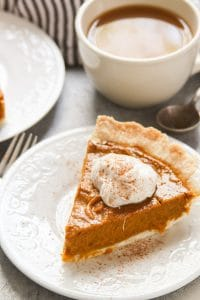 Slice of Vegan Pumpkin Pie on a Plate with Coffee Cup in the Background