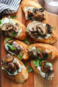 Overhead View of a Wooden Platter of Mushroom Crostini with Herbed Cashew Cheese