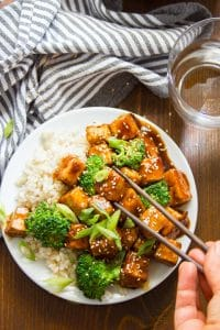 Chopsticks Grabbing a Piece of Tofu From a Plate of Teriyaki Tofu with Broccoli