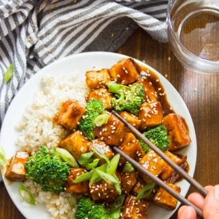 Chopsticks Grabbing a Piece of Tofu From a Plate of Teriyaki Tofu with Broccoli