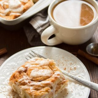 Vegan Cinnamon Roll on a Plate with Fork and Coffee Cup in the Background
