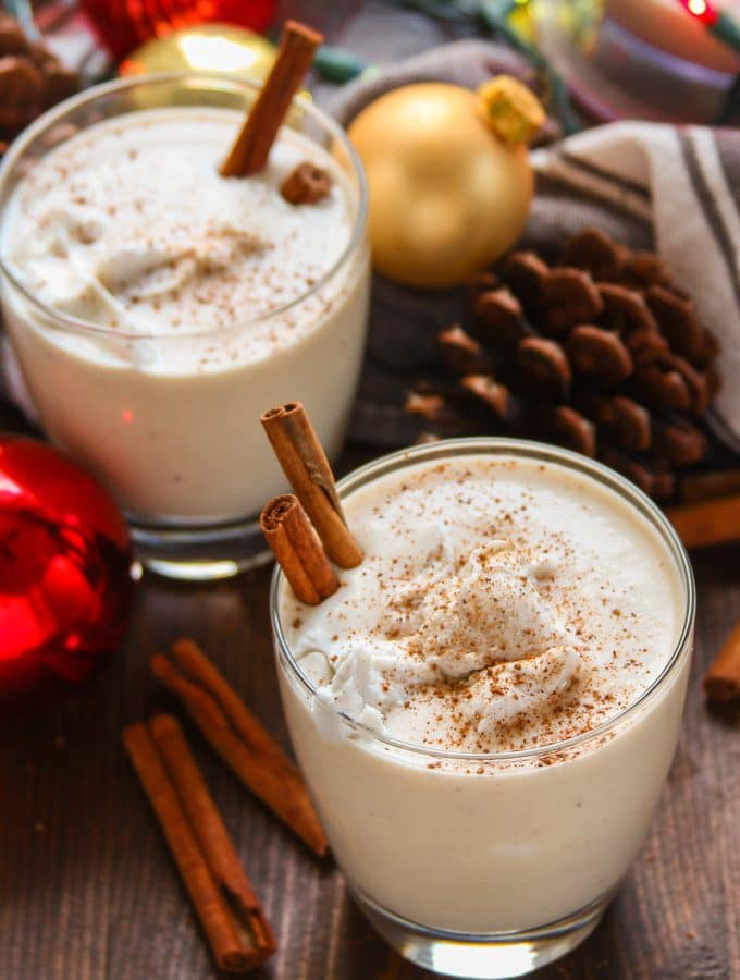 Two Glasses of Vegan Eggnog with Cinnamon Sticks, Pinecones and Christmas Lights in the Background