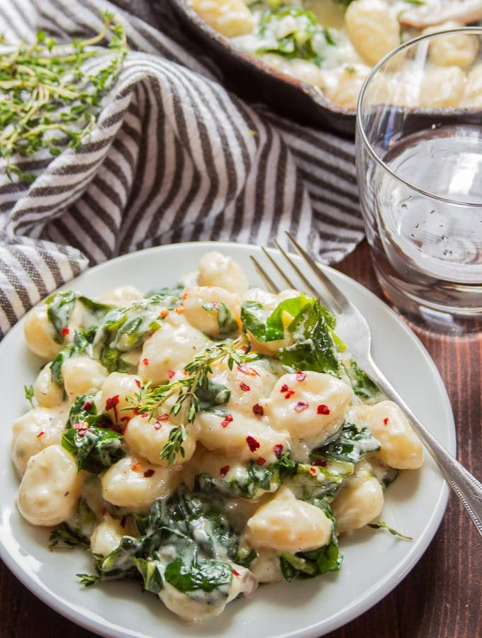 Plate of Vegan Gnocchi with Creamy Lemon Garlic Sauce with Water Glass and Skillet in the Background