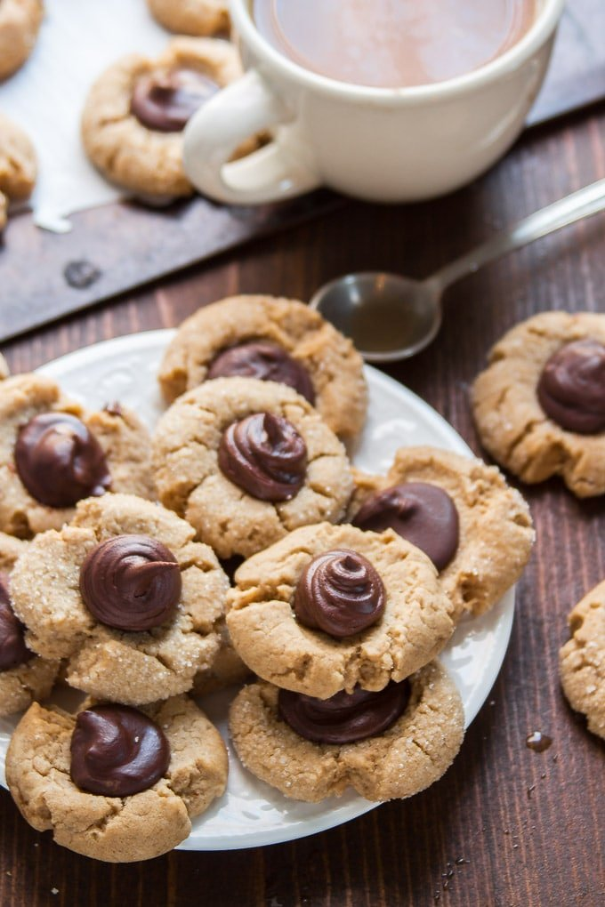 Vegan Peanut Butter Blossoms on a Plate with Coffee Cup and Spoon in the Background