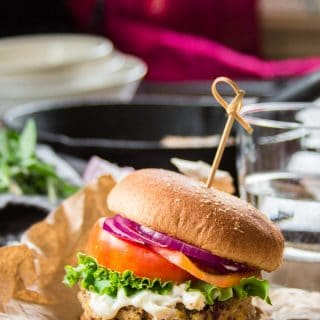 Greek Chickpea Burger on a Bun with Dishes, Water Glass and Skillet in the Background