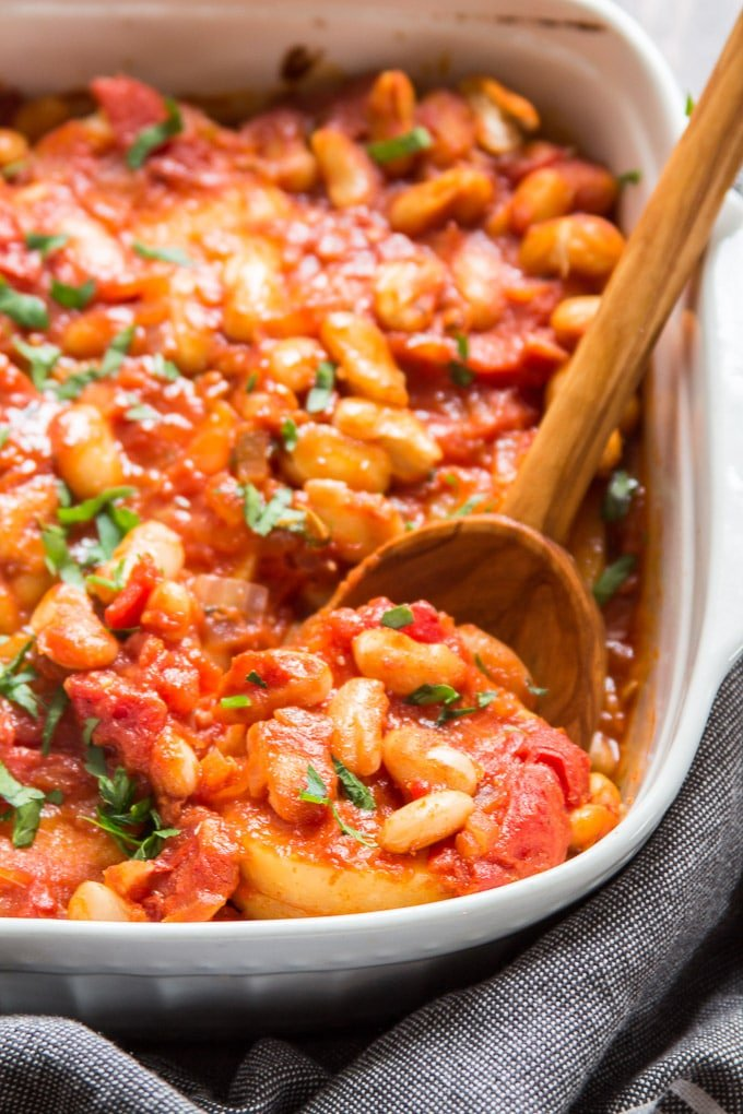 White Bean & Tomato Polenta Casserole in a Baking Dish with Serving Spoon