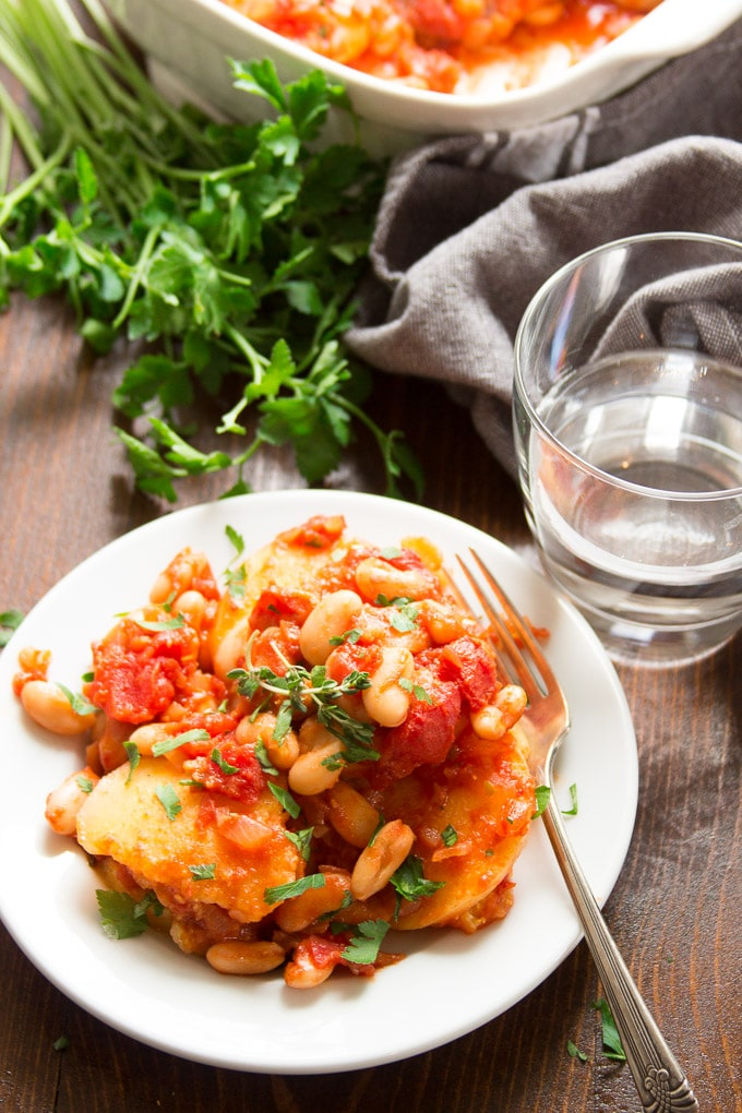 White Bean & Tomato Polenta Casserole on a Plate with Bunch of Parsley and Drinking Glass in the Background