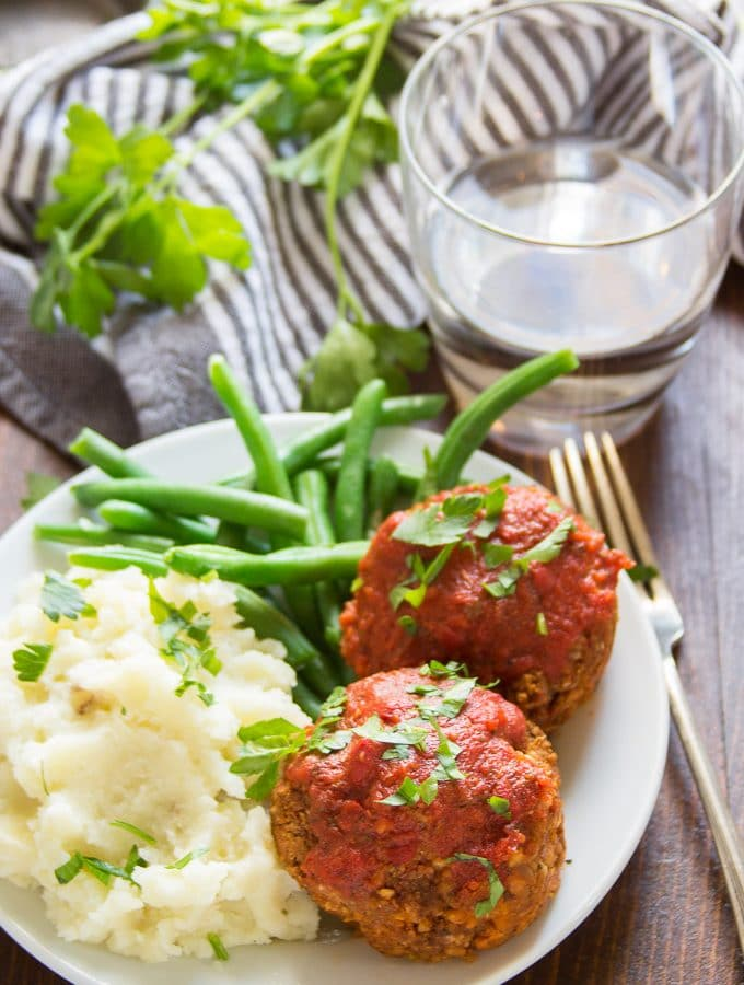 Plate Filled with Italian-Style Vegan Meatloaf Muffins, Mashed Potatoes, and Green Beans, with Napkin and Water Glass in the Background