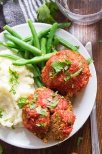 Close Up of Italian-Style Vegan Meatloaf Muffins on a Plate With Mashed Potatoes and Green Beans