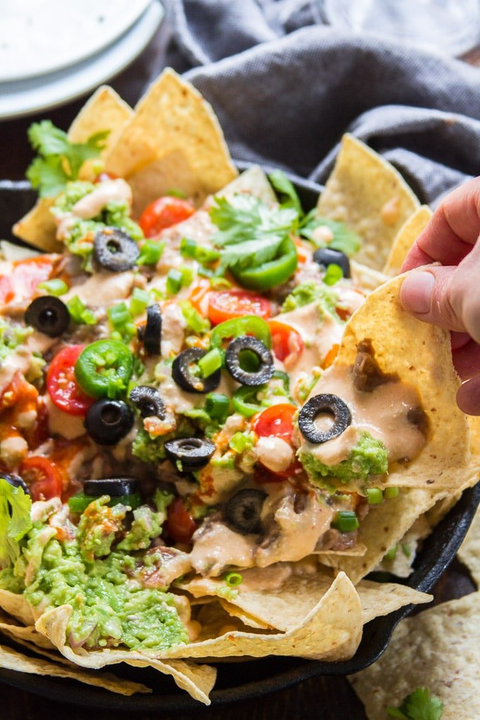 Hand Grabbing a Vegan Nacho From a Plate