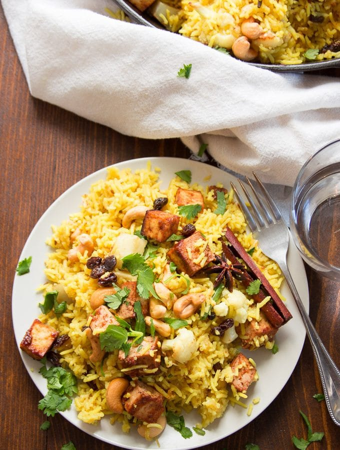 Plate of Roasted Vegetable Biryani with Baked Tofu with Fork, Napkin, and Water Glass
