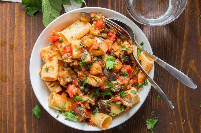 Bowl of Spicy Eggplant Pasta with a Fork, Spoon and Water Glass