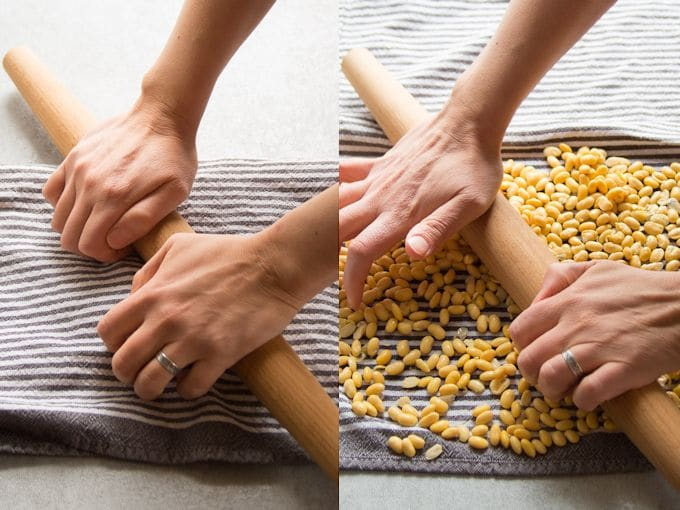 Hands Splitting Soybeans with a Rolling Pin for Making Tempeh