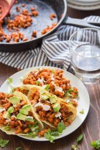 Chipotle Tempeh Tacos on a Plate with Skillet and Drinking Glass in the Background