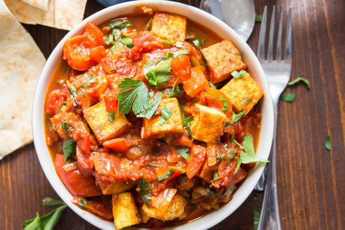 Overhead View of Vegan Shakshuka in a Bowl with a Fork and Pita Wedges