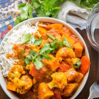 A Bowl of Sweet Potato & Vegetable Vindaloo with Water Glass and Fork