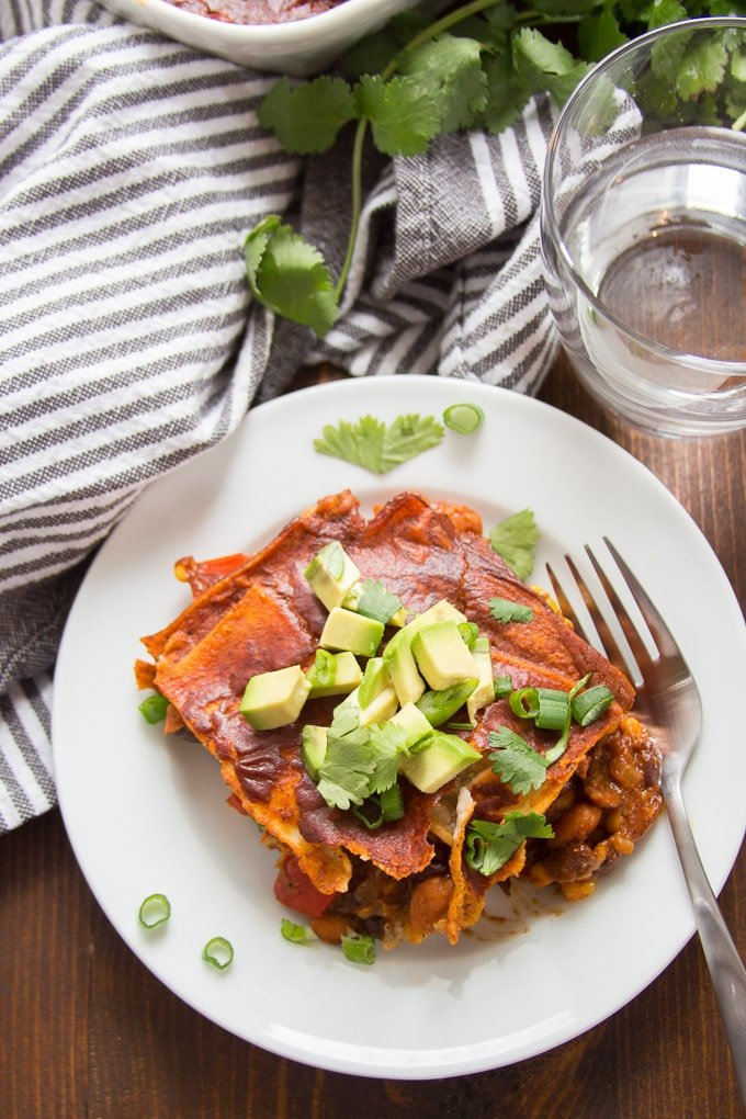 Loaded Enchilada Casserole Topped with Avocado and Cilantro on a Plate