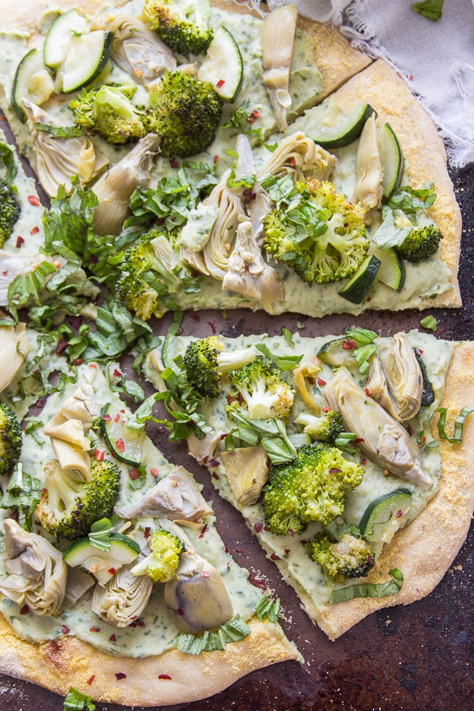 A Sliced Vegan Green Goddess Pizza Topped with Fresh Basil and Red Pepper Flakes