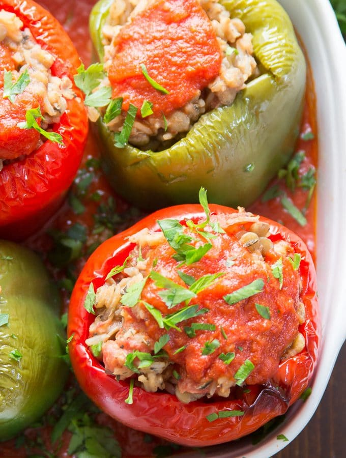 Vegan Stuffed Peppers in a Baking Dish with Marinara Sauce and Topped with Fresh Parsley