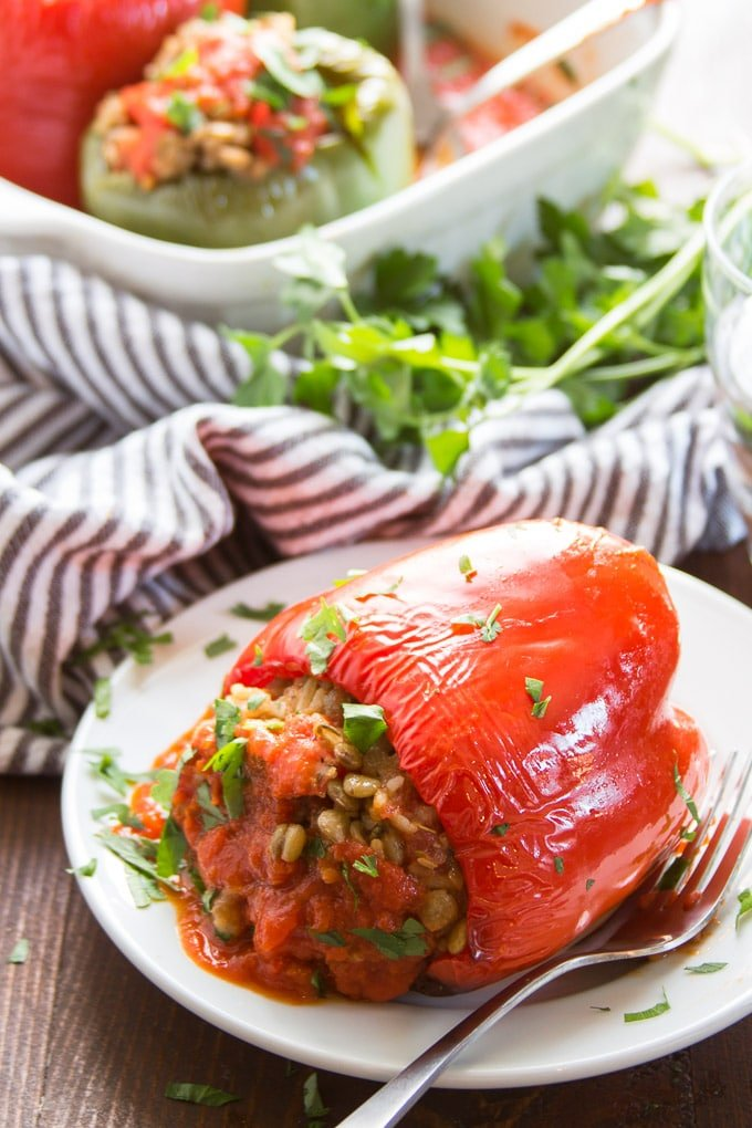 Vegan Stuffed Pepper on a Plate with Baking Dish in the Background
