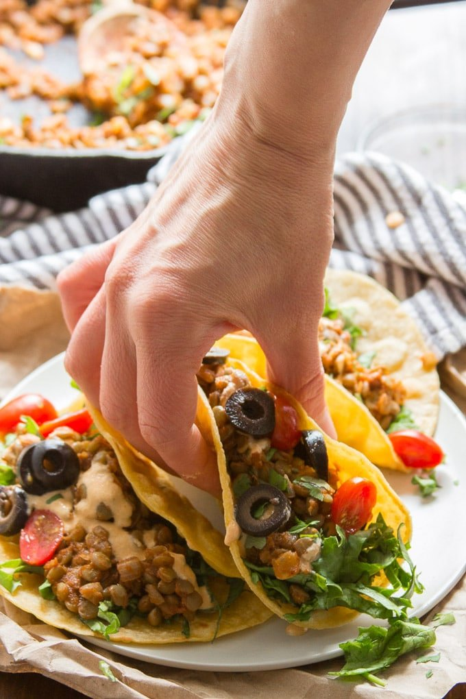 Hand Grabbing a Lentil Taco from a Plate