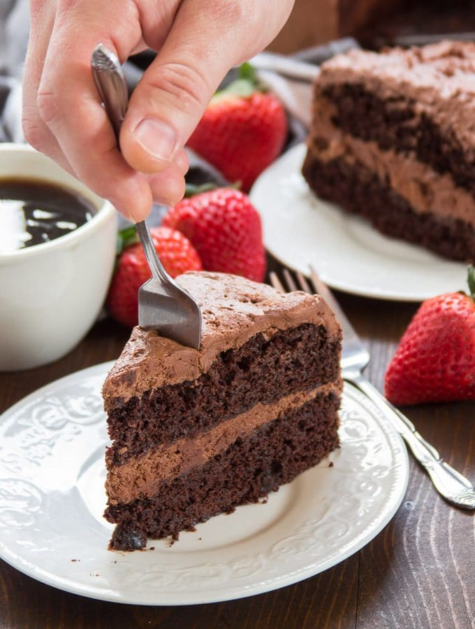 Hand Plunging a Fork into the Tip of a Slice of Vegan Chocolate Cake