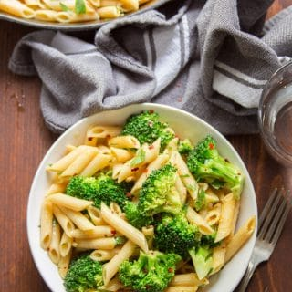 Bowl of Broccoli Pasta with Skillet, Water Glass and Tea Towel